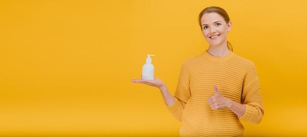 Mulher mostrando o polegar para cima gesto com líquido desinfetante para as mãos Foto Premium