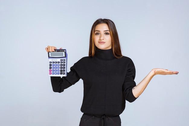 Mulher mostrando o resultado final na calculadora.