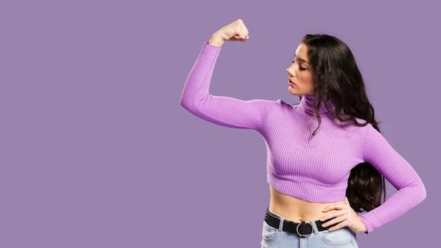 Mulher mostrando os músculos e tendo um top violeta para os lados