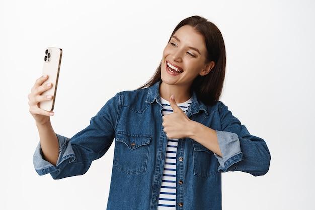 Mulher mostrando os polegares para a câmera do celular, tirando selfie, fazendo fotos ou gravando vídeos para recomendar um lugar ou loja, curtir e aprovar