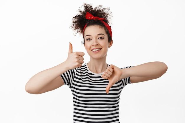 Mulher mostrando os polegares para cima e para baixo, conceito de avaliação e feedback. em pé com tiara com cabelo cacheado penteado e camiseta branca