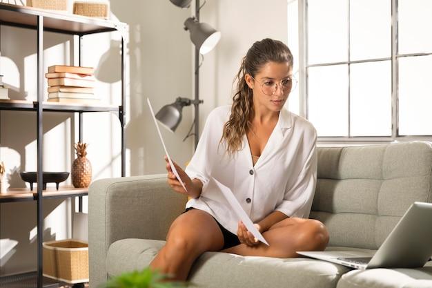 Mulher mostrando papéis no laptop