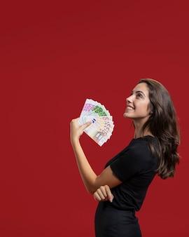 Mulher mostrando seu dinheiro de compras com espaço de cópia