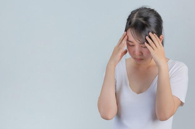 Mulher mostrando sinais de estresse em uma parede cinza