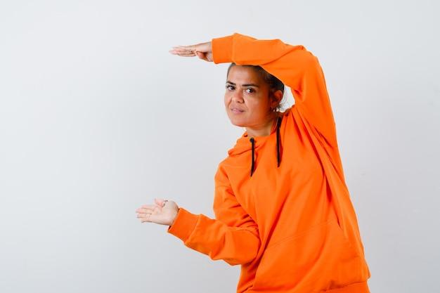 Mulher mostrando sinal de tamanho com capuz laranja e parecendo confiante