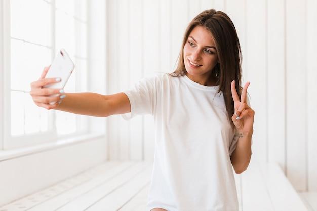 Mulher, mostrando, sinal v, e, levando, selfie