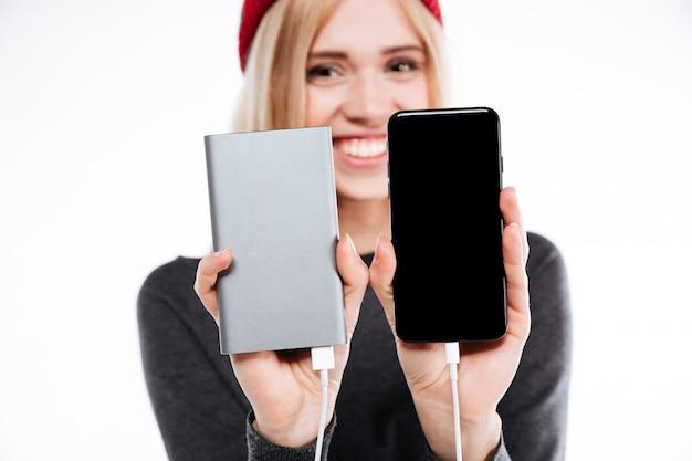 Mulher mostrando smartphone e banco de potência