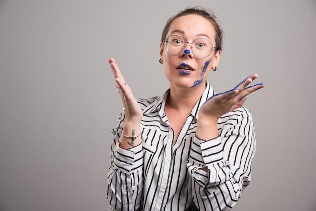 Mulher mostrando suas tintas com as mãos em cinza