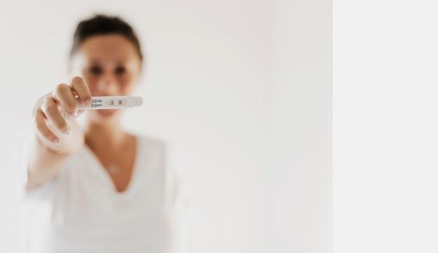 Mulher mostrando teste de gravidez positivo
