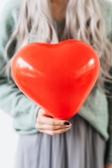 Mulher mostrando um balão vermelho de coração