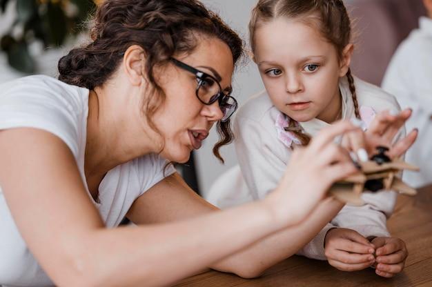 Mulher mostrando um controlador de madeira para seus alunos na aula