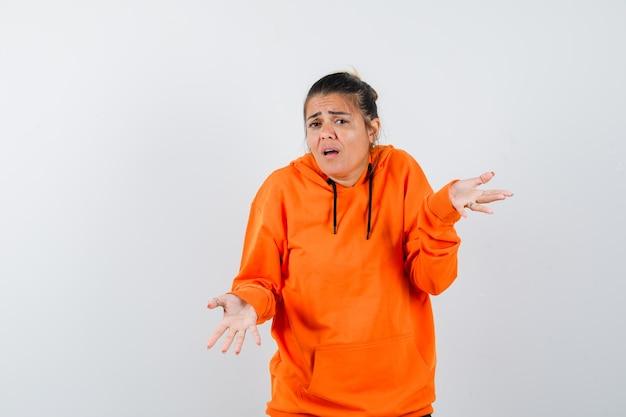 Mulher mostrando um gesto desamparado com um capuz laranja e parecendo confusa
