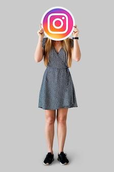 Mulher mostrando um ícone do instagram
