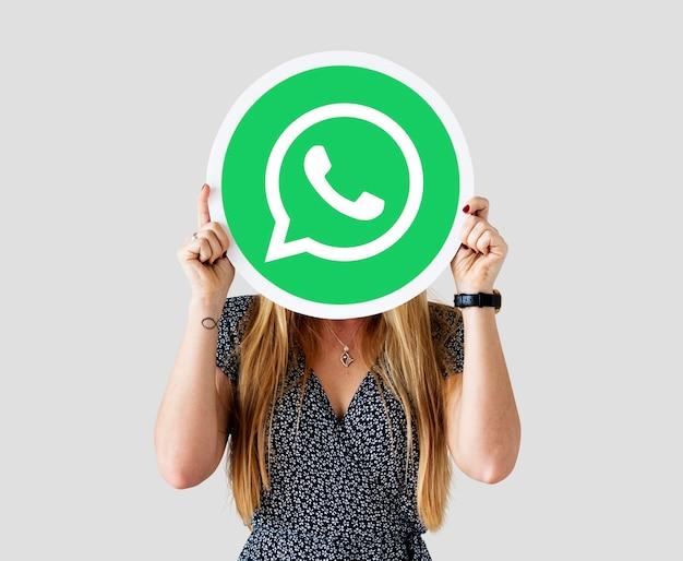 Mulher mostrando um ícone do whatsapp messenger
