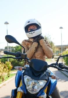 Mulher motociclista ajustando capacete, conceito de segurança na estrada