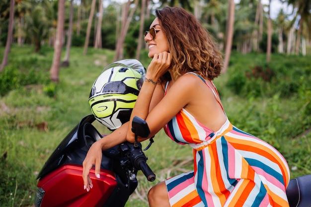 Mulher motociclista caucasiana feliz com vestido colorido de verão de férias com capacete de motociclista