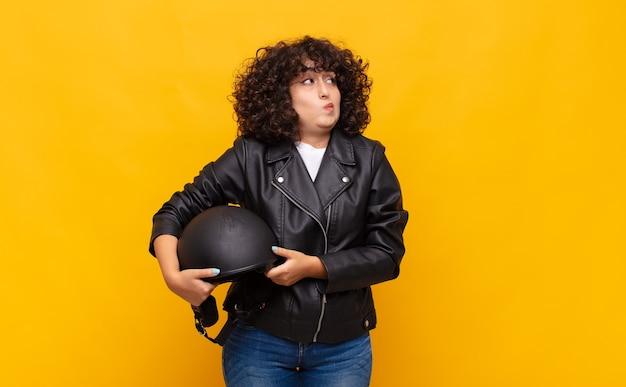 Mulher motociclista encolhendo os ombros, sentindo-se confusa e incerta, duvidando com os braços cruzados e olhar perplexo