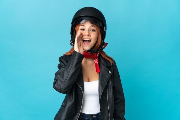 Mulher motociclista isolada no azul gritando com a boca bem aberta
