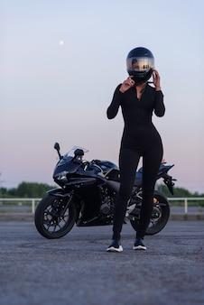 Mulher motociclista na jaqueta de couro preta e capacete facial senta-se perto de moto esportiva elegante no estacionamento urbano. viajando e conceito de estilo de vida ativo.