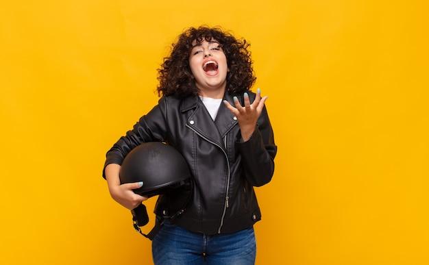 Mulher motociclista parecendo desesperada e frustrada, estressada, infeliz e irritada, gritando e gritando