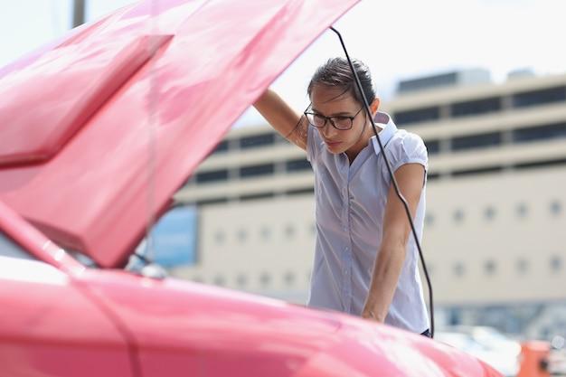 Mulher motorista abre o capô do carro e analisa o procedimento de avaria no caso de um carro