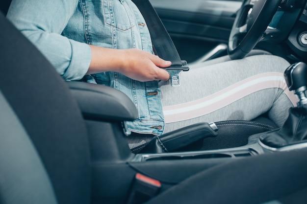 Mulher motorista apertando o cinto de segurança no carro, contra acidente de carro, conceito de segurança, transporte seguro