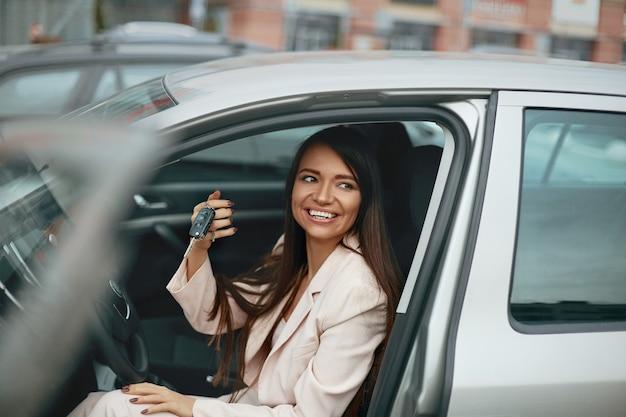 Mulher, motorista de carro sorrindo, mostrando as novas chaves do carro