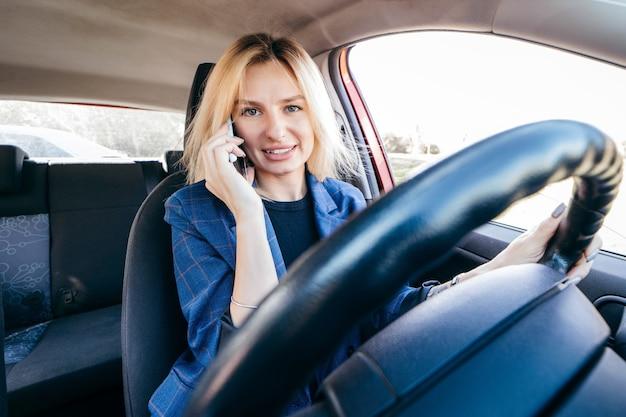 Mulher motorista dirigindo um carro distraída ao telefone e olhando para o lado