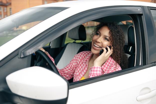 Mulher motorista usando seu telefone celular enquanto dirige o carro