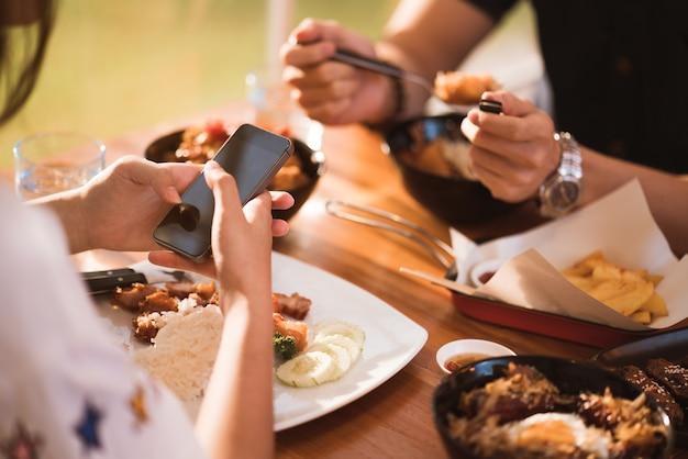 Mulher móvel ao jantar com amigos no restaurante