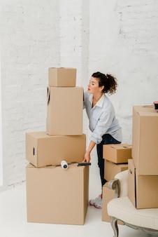 Mulher movendo pilha de caixas