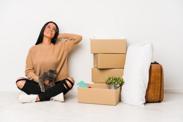 Mulher movendo-se para casa em branco tocando a parte de trás da cabeça, pensando e fazendo uma escolha.