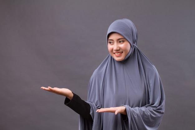 Mulher muçulmana apontando a mão para o espaço em branco