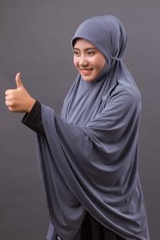 Mulher muçulmana apontando o polegar para cima, modelo de mulher islâmica asiática