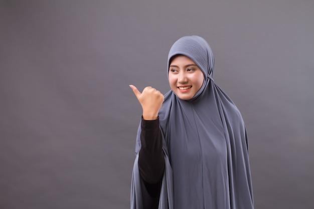 Mulher muçulmana apontando o polegar para um espaço em branco