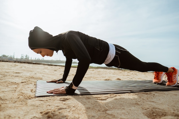 Mulher muçulmana apta a fazer flexões ao ar livre