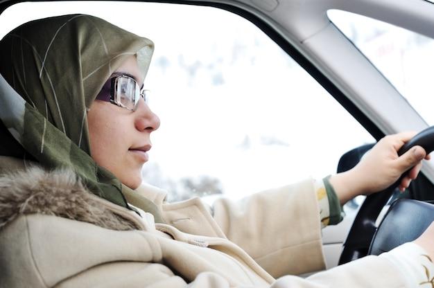 Mulher muçulmana árabe dirigindo carro com lenço tradicional