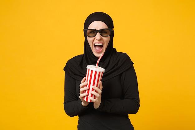 Mulher muçulmana árabe em roupas pretas de hijab óculos 3d imax assistir filme filme segurar copo de papel de refrigerante isolado no retrato de parede amarela. conceito de estilo de vida de pessoas. .