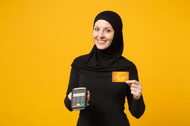 Mulher muçulmana árabe em roupas pretas de hijab segura o terminal de pagamento para processar e adquirir pagamentos com cartão de crédito isolados na parede amarela. conceito de estilo de vida religioso de pessoas.