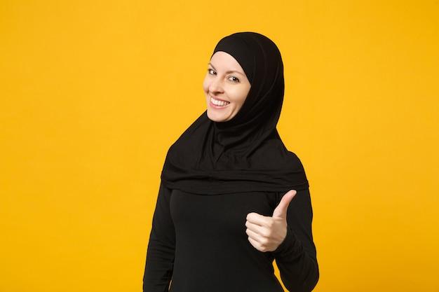 Mulher muçulmana árabe jovem sorridente em roupas pretas de hijab aparecendo os polegares, isolado na parede amarela, retrato. conceito de estilo de vida religioso de pessoas.