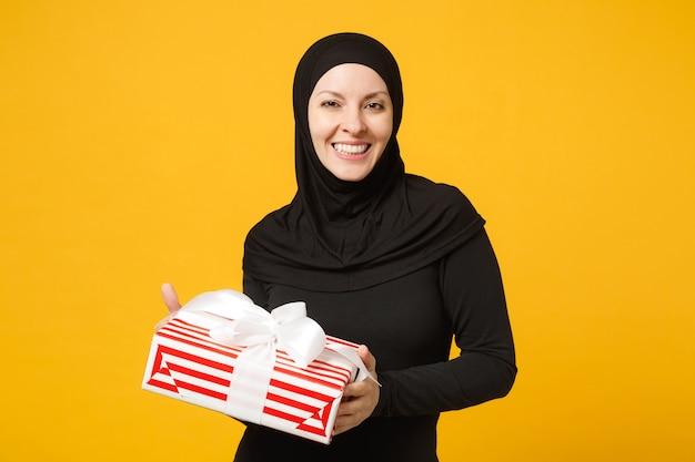 Mulher muçulmana árabe jovem sorridente em roupas pretas de hijab segura na mão caixa de presente com presente isolado no retrato de parede amarela. conceito de estilo de vida religioso de pessoas. .