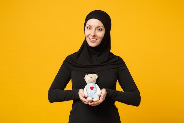 Mulher muçulmana árabe jovem sorridente em roupas pretas de hijab segura nas mãos ursinho de pelúcia brinquedo isolado no retrato de parede amarela. conceito de estilo de vida religioso de pessoas.