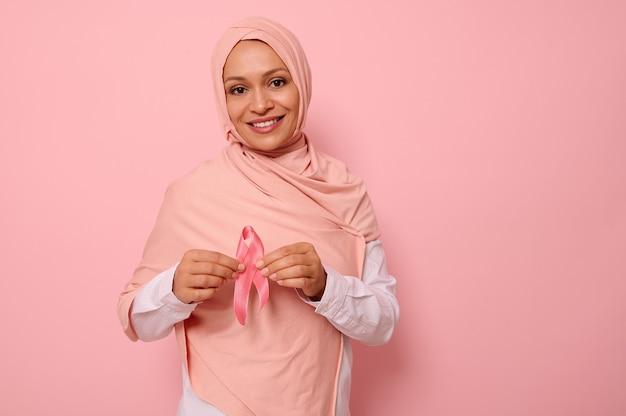 Mulher muçulmana árabe simpática e solidária com um hijab rosa segura uma fita rosa na altura do peito para uma campanha contra o câncer de mama, promovendo a conscientização sobre o câncer. mês rosa de outubro, conceito de saúde feminina