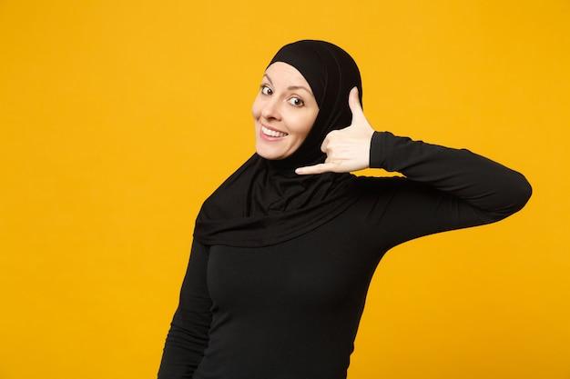 Mulher muçulmana árabe sorridente com roupas pretas de hijab, fazendo gestos de telefone, como diz me ligue de volta isolado na parede amarela, retrato. conceito de estilo de vida do islã de pessoas.