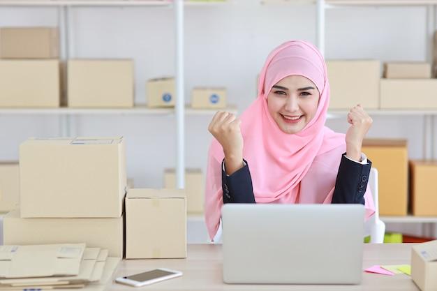 Mulher muçulmana asiática ativa em terno azul, sentado e trabalhando com computador e entrega de caixa de pacote online. garota de trabalho freelance de pequena empresa de inicialização olhar para a câmera com emoção emocionante.