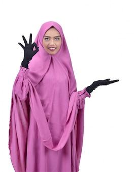 Mulher muçulmana asiática atraente mostrando o espaço vazio para copyspace
