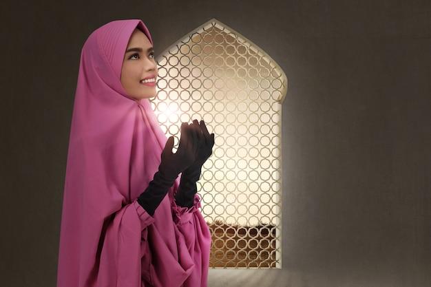 Mulher muçulmana asiática bonita, levantando a mão e rezando
