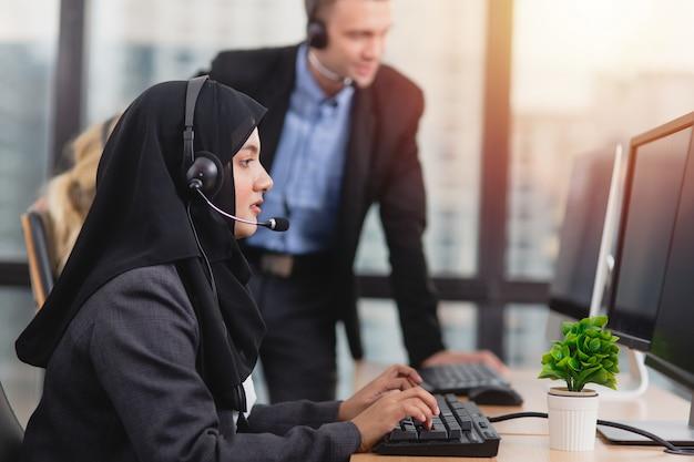 Mulher muçulmana asiática bonita nova que trabalha a equipe de atendimento ao cliente do consultor da mesa de serviço que fala no fone de ouvido no call center