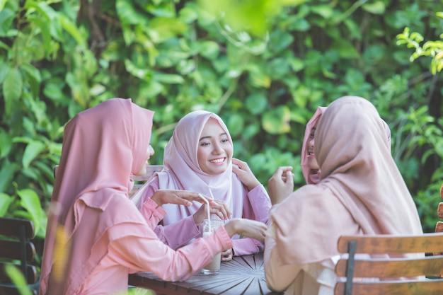 Mulher muçulmana asiática bonita se divertindo no café junto com amigos