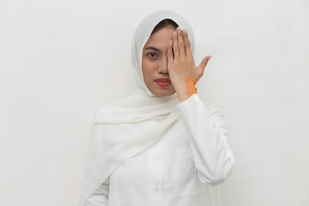 Mulher muçulmana asiática cobrindo um olho com a mão
